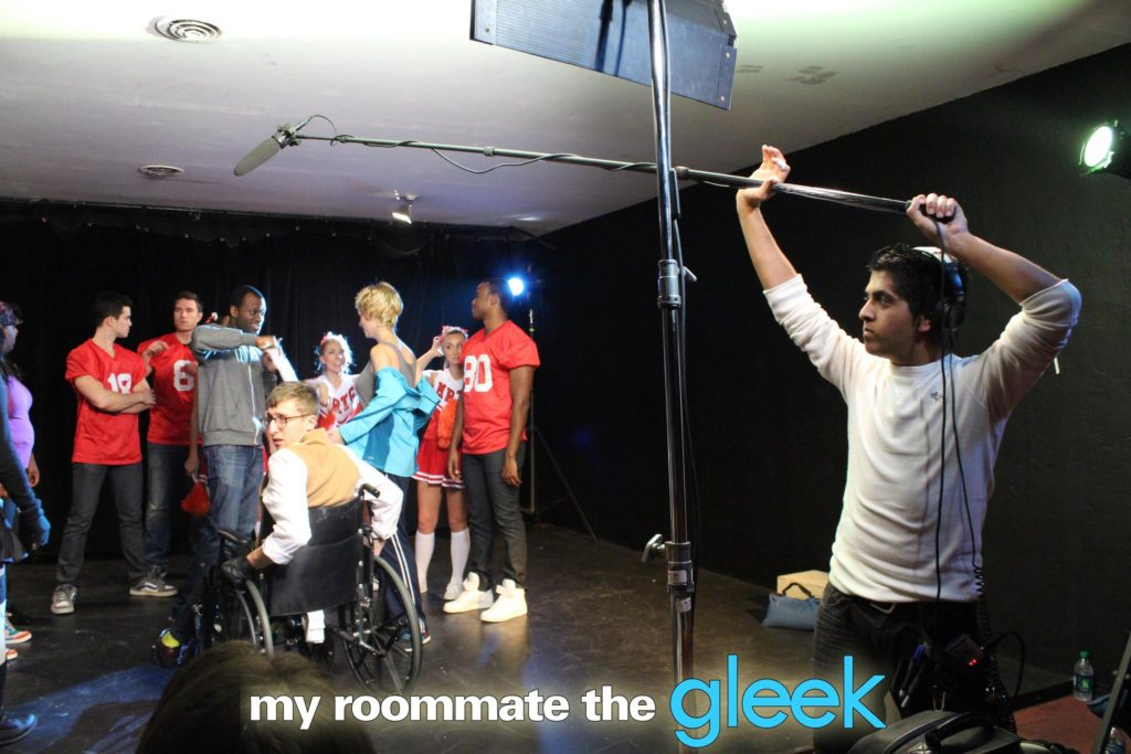 "Sound technician Ernesto Ruvalcaba boom operating on the set of ""my roommate the Gleek""."